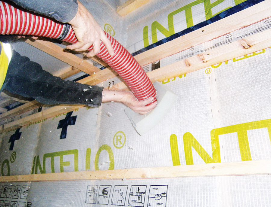 Cellulose insulation is pumped into the timber frame walls