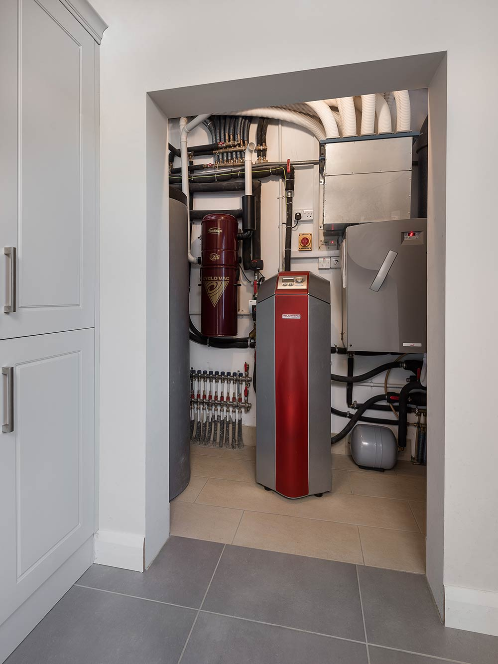 The house's utility space includes the Zehnder Comfoair 550 heat recovery ventilation system, the Heliotherm brine-to-water heat pump that supplies underfloor heating on both floors, and a 500 litre domestic hot water tank with fresh hot water heat exchanger.
