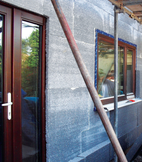External wall insulation showing door overlapped by first layer and second layer being installed