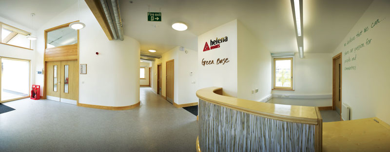 The reception area with desk featuring recycled materials and expressed ventilation ductwork