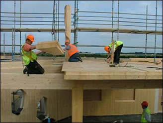 Workers fit timber floor panels on the building's 3rd floor