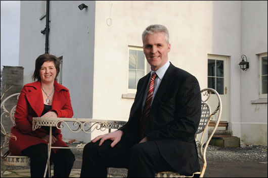 The clients, Neil and Kyra Orr, relaxing in their front courtyard, are able to reflect on a job well done