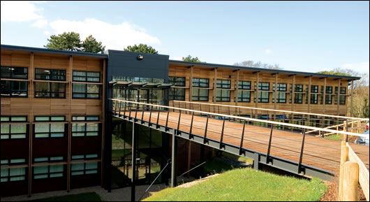 A commitment to conserving the environment in a broader sense was vital for the Orchard building, and two-thirds of the external cladding is cedar wood which blends well with the building's setting. Located in an eighteen acre woodland, the building's main entrance is across a footbridge