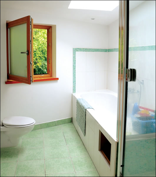 Opaque glass was chosen in the bathroom partly to filter light. Note the laundry chute