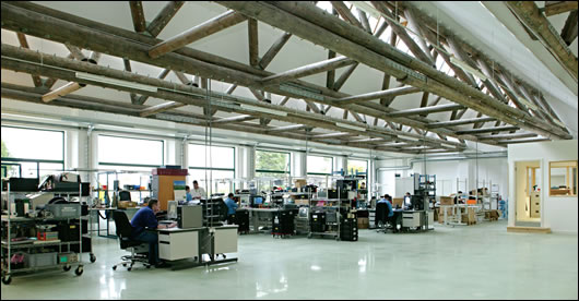 Timber trusses dominate the extensively glazed north-facing factory floor, which was polished mechanically, thus avoiding the use of any chemical products or additional materials