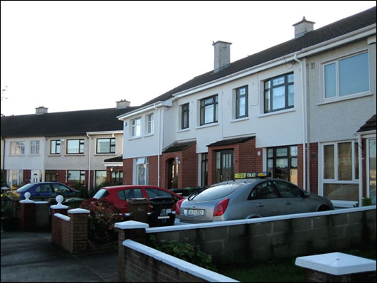 A terrace in North Dublin (below) where three householders externally insulated with a brick-like render finish (above) to base and a napp finish render