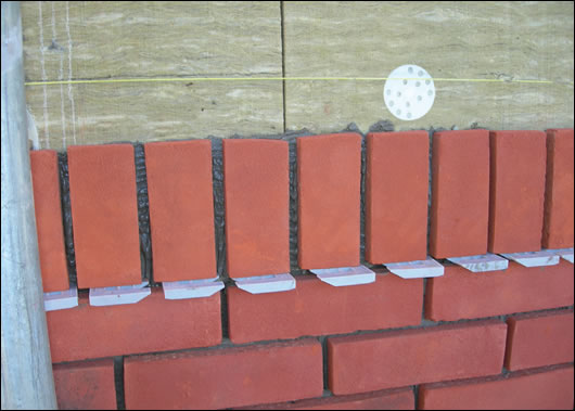 (below and above) Ibstock's Brickshield system, with Rockwool high density external insulation coated in the company's adhesive mortar, before Ibstock brick slips are applied