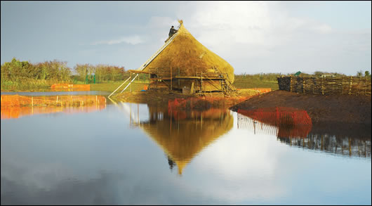 The crannog - showing its waterside position and dominant thatch roof