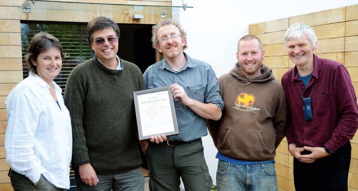 (left to right) Architect Janet Cotterell & client Adam Dadeby receive the passive house certificate from builder Jonathan Williams, pictured with build team member Joe Bellows with passive house certifier Peter Warm